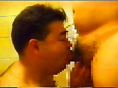 Two plump Asian men making blowjobs in turn in a shower